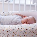 Scandi Spot Baby Bed - baby asleep on side