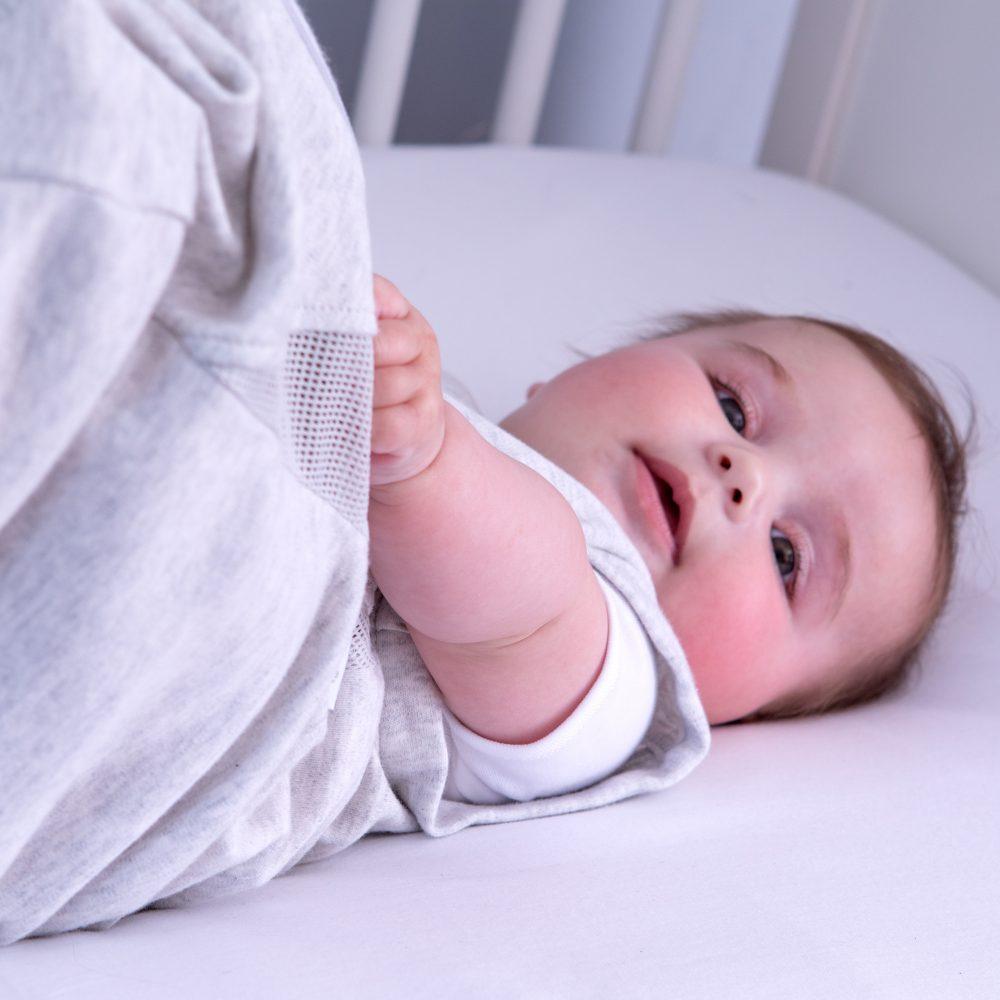 Baby in grey Purflo baby sleep bag in cot